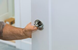 Male carpenter fixing lock in door with home hand close-up.